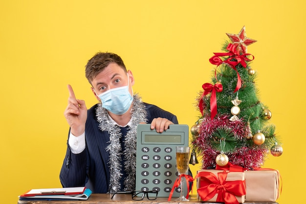 Vorderansicht des geschäftsmannes mit maske, die auf rechner zeigt, der am tisch nahe weihnachtsbaum sitzt und auf gelb präsentiert