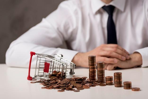 Vorderansicht des geschäftsmannes mit münzen und einkaufswagen