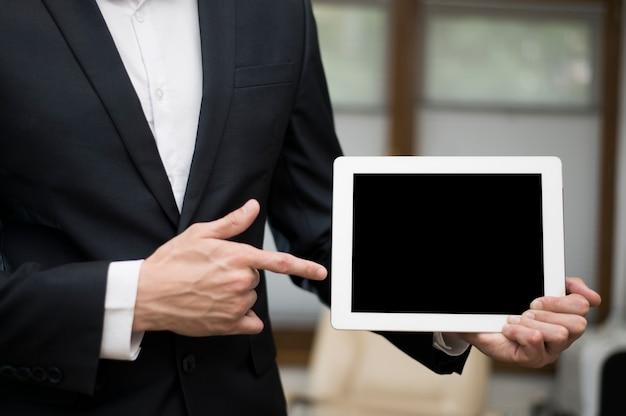 Vorderansicht des geschäftsmannes zeigend auf tablette