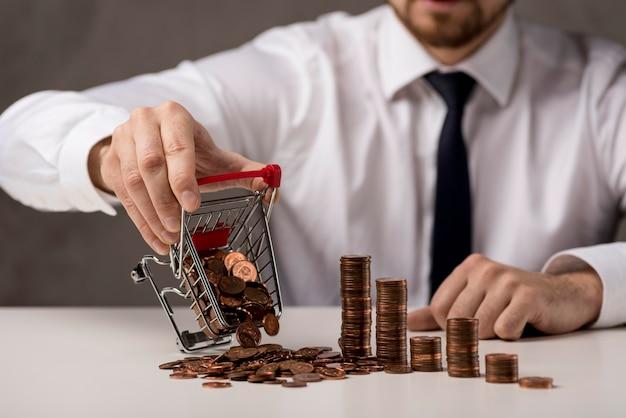 Vorderansicht des geschäftsmanns, der einkaufswagen von münzen verschüttet