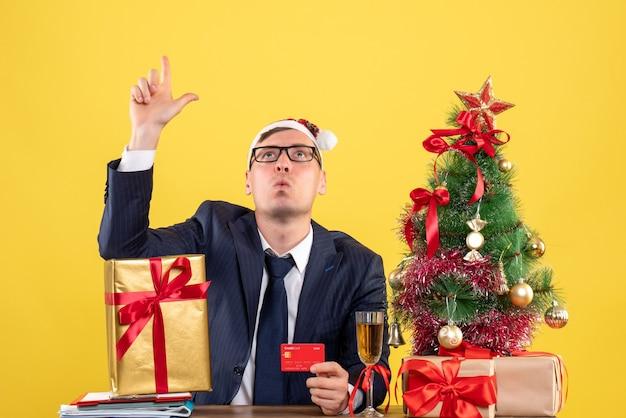 Vorderansicht des geschäftsmanns, der oben sitzt am tisch nahe weihnachtsbaum und geschenke auf gelb