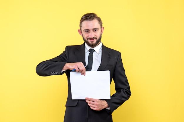 Vorderansicht des geschäftsmanns des jungen mannes in einem anzug, der lächelt und leeres papier in der mitte auf gelb hält
