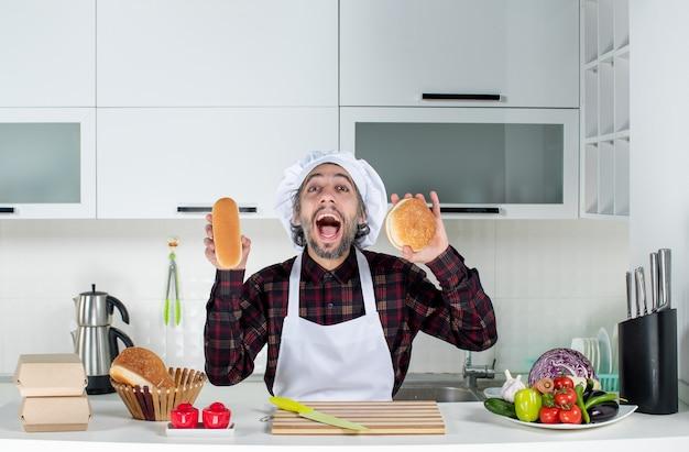 Vorderansicht des geschrienen männlichen kochs, der brot in der küche hält