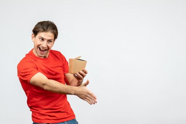 Vorderansicht des glücklichen jungen kerls in der roten bluse, die kleine box hält und jemanden auf weißem hintergrund begrüßt