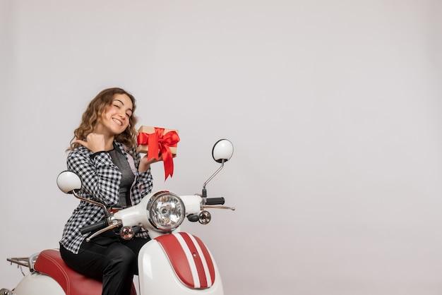 Vorderansicht des glücklichen jungen mädchens auf moped, das geschenk auf grauer wand hält
