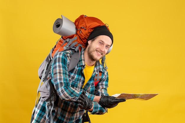 Vorderansicht des glücklichen jungen rucksacktouristen mit dem schwarzen hut, der karte hält