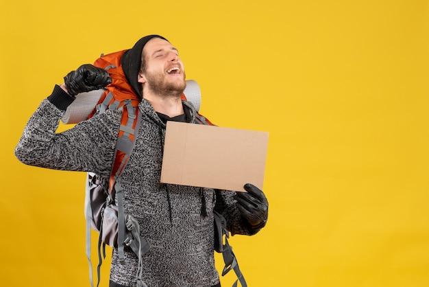 Vorderansicht des glücklichen männlichen anhängers mit lederhandschuhen und rucksack, die leeren karton halten