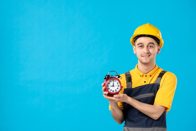 Vorderansicht des glücklichen männlichen arbeiters in der uniform mit uhren auf der blauen wand