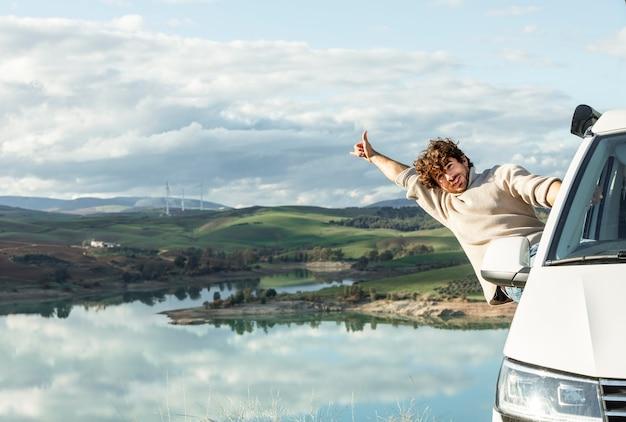 Vorderansicht des glücklichen mannes, der natur während auf einer straßenreise genießt