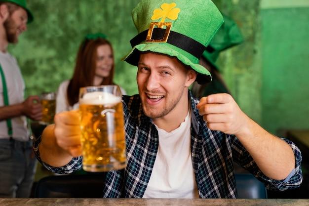 Vorderansicht des glücklichen mannes mit hut, der st feiert. patricks tag an der bar