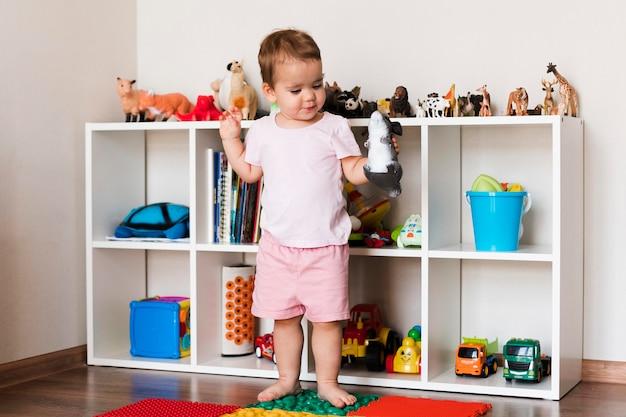 Vorderansicht des glücklichen niedlichen jungen, der mit spielzeugen spielt