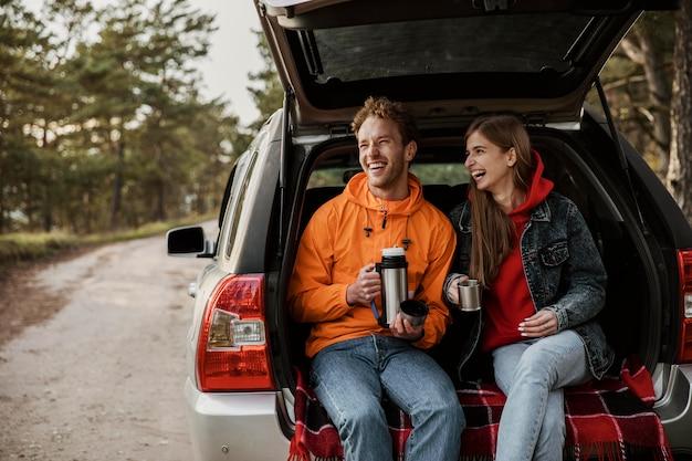 Vorderansicht des glücklichen paares, das heißes getränk im kofferraum des autos genießt