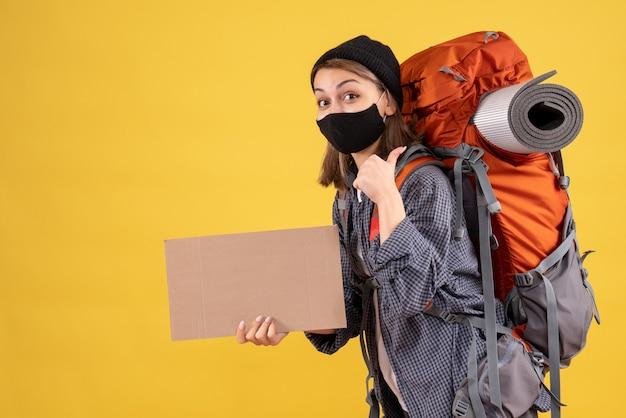Vorderansicht des glücklichen reisenden mädchens mit schwarzer maske und rucksack, die pappe halten