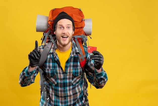 Vorderansicht des glücklichen wohnmobils mit backpacker, der kreditkarte hält, die zur decke zeigt