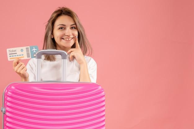 Vorderansicht des glückseligen jungen mädchens mit dem rosa koffer, der ticket hält
