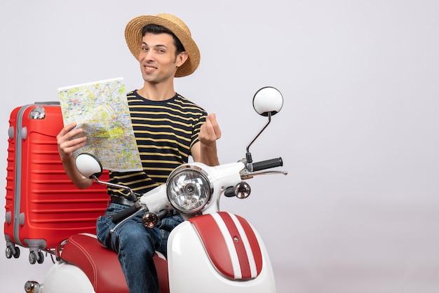 Vorderansicht des glückseligen jungen mannes mit strohhut auf moped, das karte hält