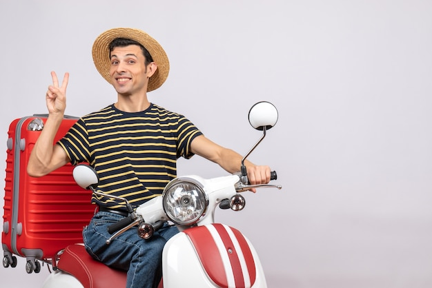Vorderansicht des glückseligen jungen mannes mit strohhut auf moped gestikulierendes siegeszeichen