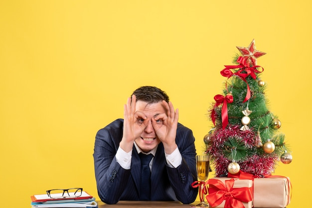 Vorderansicht des gut aussehenden mannes, der ok zeichenauge zeigt, das am tisch nahe weihnachtsbaum sitzt und auf gelb präsentiert