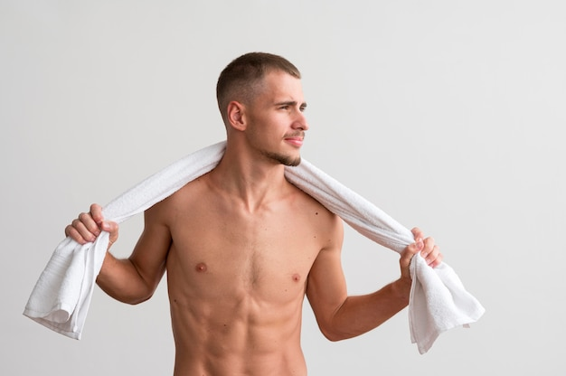 Vorderansicht des gutaussehenden mannes, der mit handtuch aufwirft