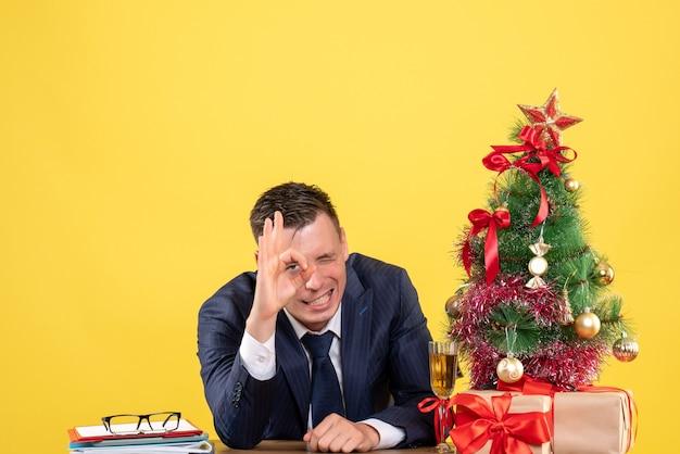 Vorderansicht des gutaussehenden mannes, der okey zeichenauge zeigt, das am tisch nahe weihnachtsbaum sitzt und auf gelb präsentiert