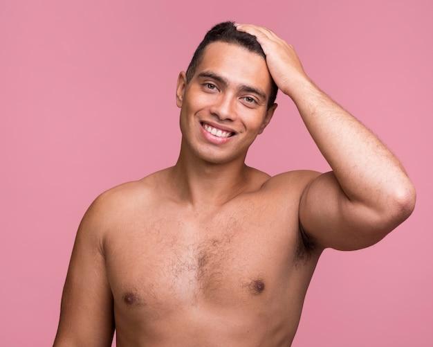 Vorderansicht des gutaussehenden mannes des smileys, der hemdlos aufwirft