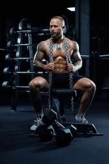 Vorderansicht des hemdlosen bodybuilders, der auf bank mit hanteln auf boden sitzt.