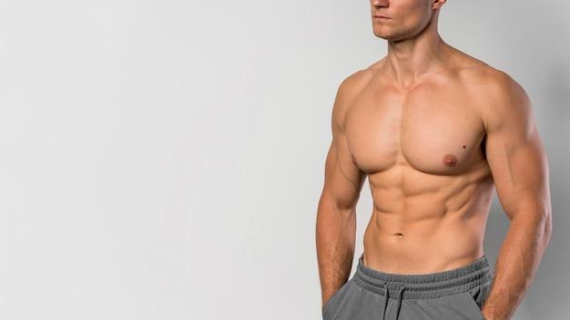 Vorderansicht des hemdlosen fit mannes, der mit kopienraum aufwirft