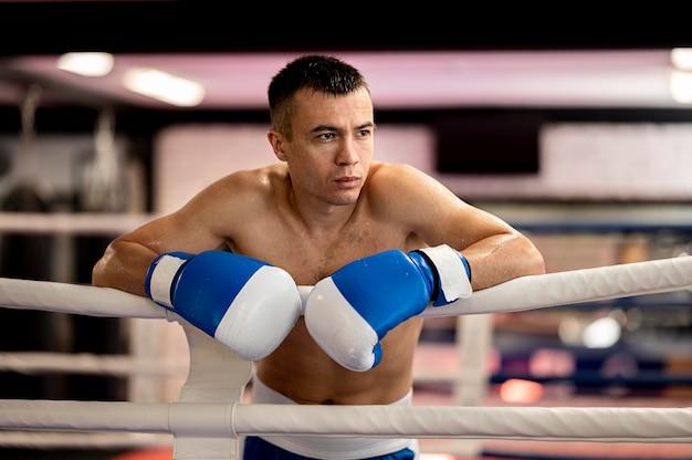 Vorderansicht des hemdlosen männlichen boxers im ring