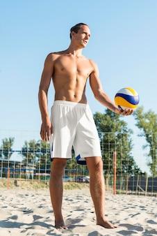 Vorderansicht des hemdlosen männlichen volleyballspielers am strand mit ball