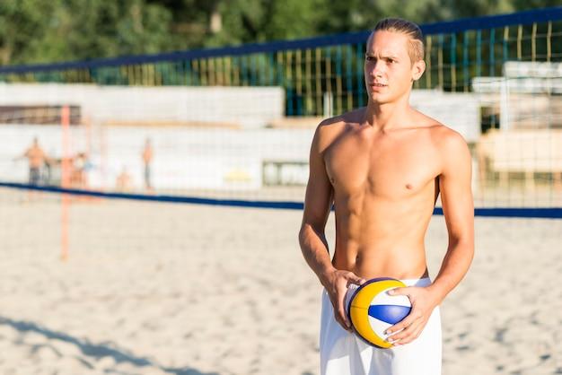 Vorderansicht des hemdlosen männlichen volleyballspielers auf dem strand, der ball hält