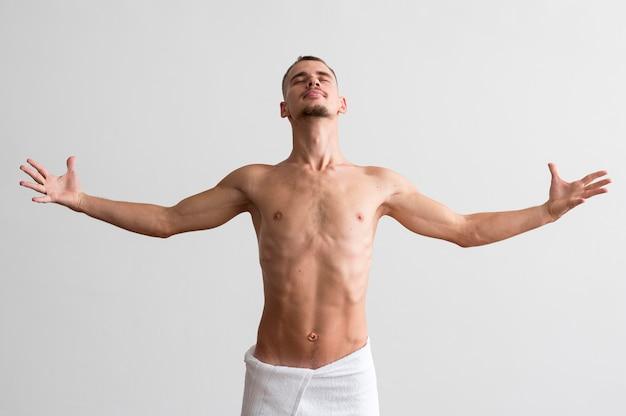 Vorderansicht des hemdlosen mannes, der in einem handtuch aufwirft