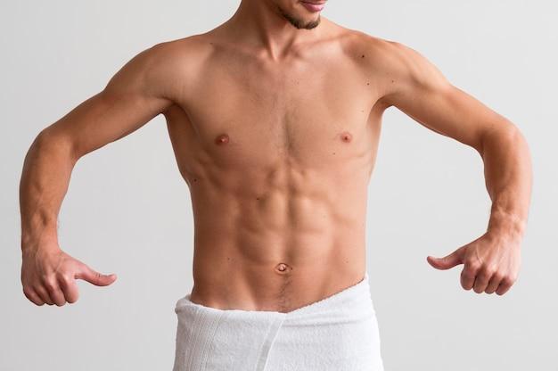 Vorderansicht des hemdlosen mannes, der seine bauchmuskeln vorführt
