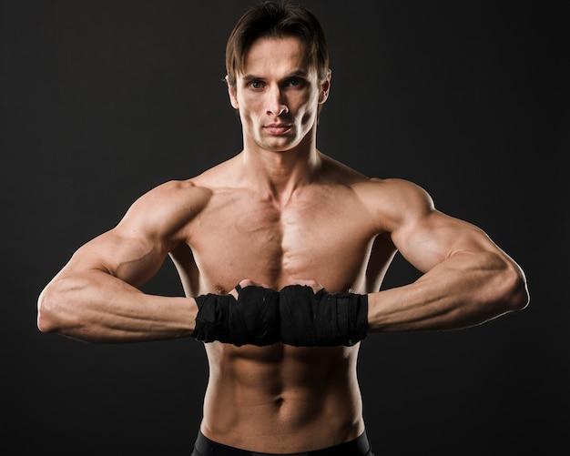 Vorderansicht des hemdlosen mannes mit muskeln, der mit boxhandschuhen aufwirft