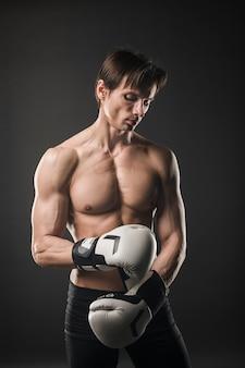 Vorderansicht des hemdlosen muskulösen mannes mit boxhandschuhen