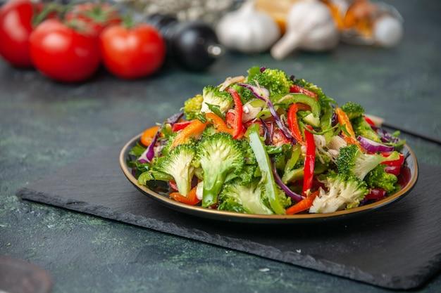 Vorderansicht des hölzernen hammers der weißen blume des frischen gemüses und des köstlichen veganen salats auf dunklem farbhintergrund