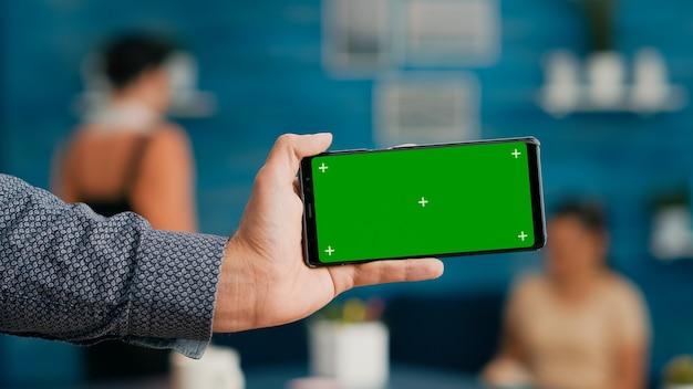 Vorderansicht des horizontalen, isolierten mock-up-greenscreen-chroma-key-displays des modernen smartphones. geschäftsfrau, die isoliertes telefon zum surfen in sozialen netzwerken verwendet, das auf dem schreibtisch sitzt