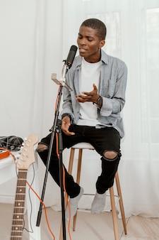 Vorderansicht des hübschen männlichen musikers, der zu hause mit mikrofon singt