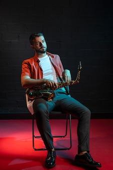 Vorderansicht des hübschen musikers, der auf stuhl sitzt, während saxophon hält