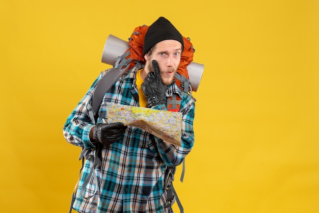 Vorderansicht des interessierten jungen rucksacktouristen mit lederhandschuhen, die karte halten