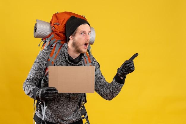 Vorderansicht des interessierten männlichen anhängers mit lederhandschuhen und rucksack, der leeren karton hält, der auf etwas zeigt