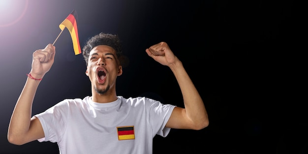 Vorderansicht des jubelnden mannes, der deutsche flagge hält