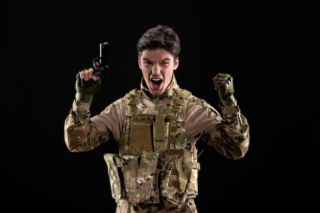 Vorderansicht des jubelnden militärs in uniform mit pistole auf schwarzer wand