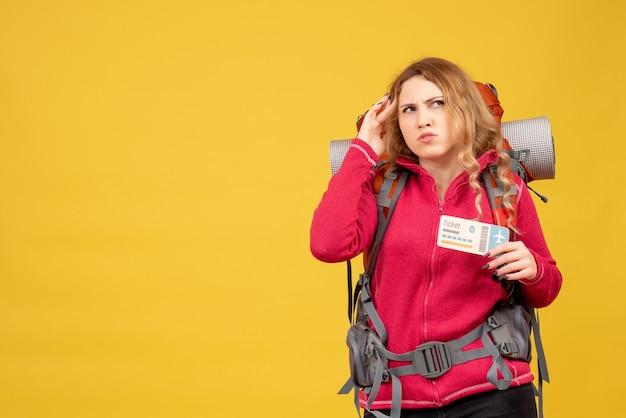 Vorderansicht des jungen denkenden emotionalen reisenden mädchens in der medizinischen maske, die ticket hält
