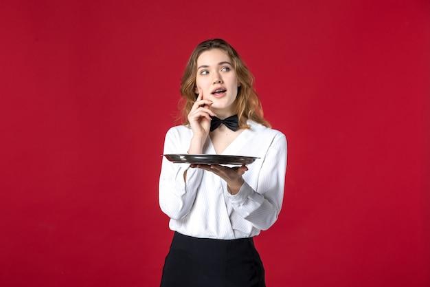 Vorderansicht des jungen, denkenden kellnerinnenschmetterlings am hals und hält tablett auf rotem hintergrund