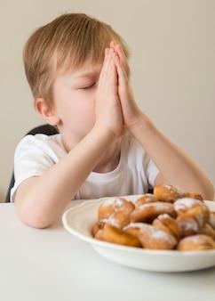 Vorderansicht des jungen, der vor dem essen betet