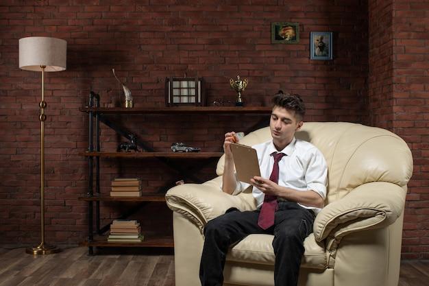 Vorderansicht des jungen geschäftsmannes, der auf sofa sitzt, das vom heft innerhalb des arbeitsbüros des raumarbeiters liest