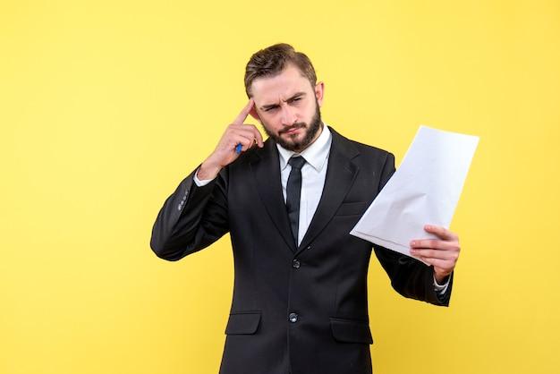 Vorderansicht des jungen geschäftsmanns des jungen mannes, der seinen zeigefinger über den hellen verstand der stirn drückt, der sich mit aufgaben auf gelb befasst