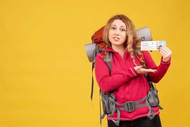 Vorderansicht des jungen glücklichen zufriedenen reisenden mädchens in der medizinischen maske, die ticket hält