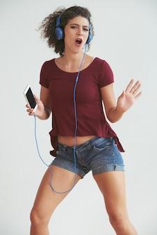 Vorderansicht des jungen mädchens tanzend zum lieblingslied auf ihrer smartphonewiedergabeliste