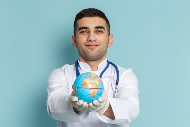 Vorderansicht des jungen männlichen arztes im weißen anzug mit blauem stethoskop, das globus hält